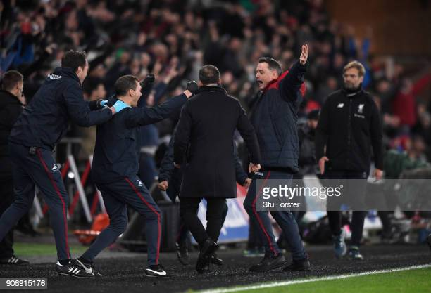 The Swansea bench celebrate on the final whistle as Jurgen Klopp looks on during the Premier League match between Swansea City and Liverpool at...
