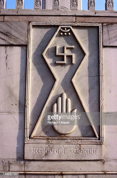 the swastika and open palm carved on the walls of the digambara jain temple. the swastika symbol is second only to the om in hindu divinity. the word swastika means auspicious in the sanskrit language. - digambara stock-fotos und bilder