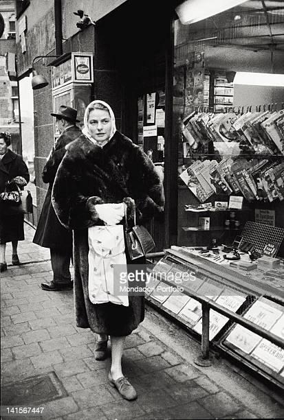 The Swedish actress Ingrid Berman walking passing in front of a newspaper kiosk Stockholm 1959