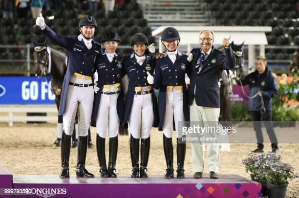 The Swedish dressage riders Patrik Kittel Therese Nilshagen Tinne Vilhelmson Silfven Rose Mathisen and team coach Bo Jena celebrating their bronce...
