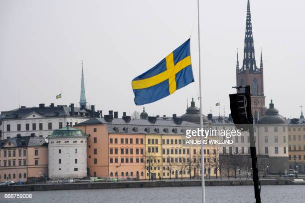 The Swedish flag at half mast is pictured at the Stockholm City Hall prior an official ceremony and a minute of silence to commemorate the victims of...