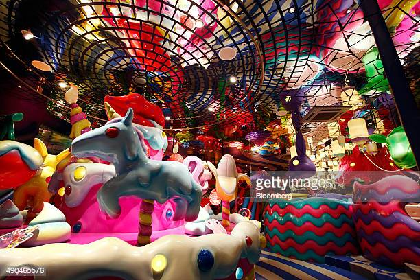 The Sweets Go Round merrygoround left stands at the entrance to the Kawaii Monster Cafe operated by Diamond Dining Co in this photograph taken with a...