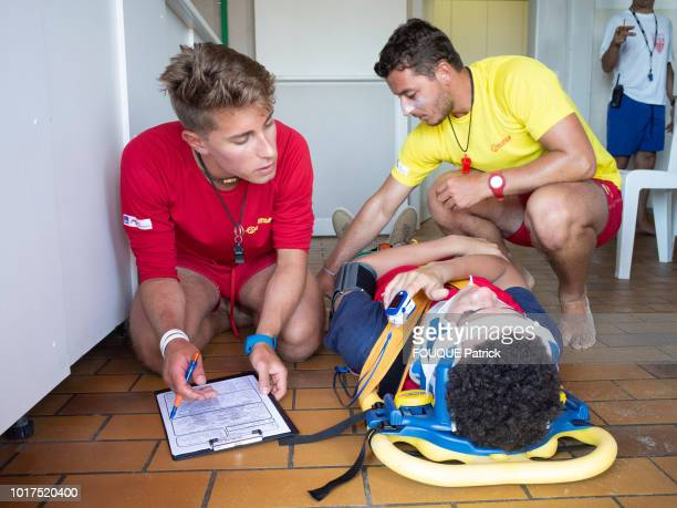 the swimmer lifeguards are photographed for Paris Match giving first aid to a wounded young man on june 07 2018 in Biscarrosse France