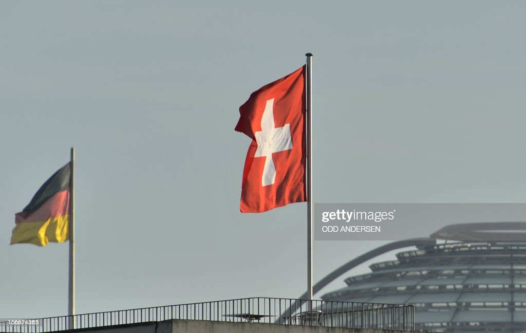 The Swiss flag flutters on the Swiss embassy as the German flag can be seen on the Reichstag building housing the lower house of parliament on November 23, 2012 in Berlin