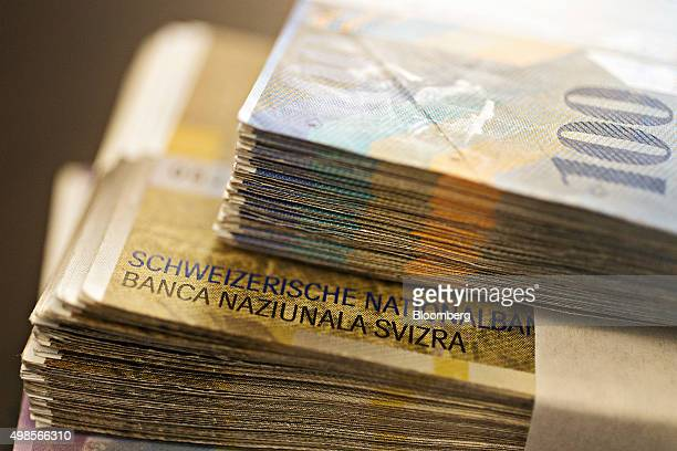 The Swiss National Bank name sits on bundles of Swiss Franc banknotes in the office of a bank in this arranged photograph in Zurich Switzerland on...