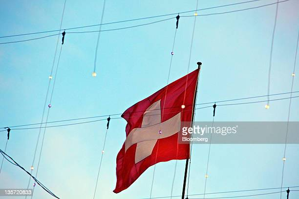The Swiss national flag flies above buildings in Zurich Switzerland on Monday Dec 12 2011 Switzerland's economy is cooling as the franc's strength is...