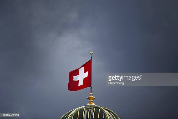 The Swiss national flag flies above the Federal Palace Switzerland's parliament building in Bern Switzerland on Tuesday March 12 2013 The Swiss...