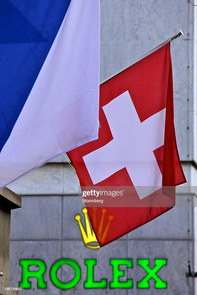 The Swiss national flag, right, sits above the Rolex store in Zurich, Switzerland, on Monday, Dec. 12, 2011. Switzerland's economy is cooling as the franc's strength is making exports more expensive just as the euro region edges toward a recession. Photographer: Gianluca Colla/Bloomberg via Getty Images