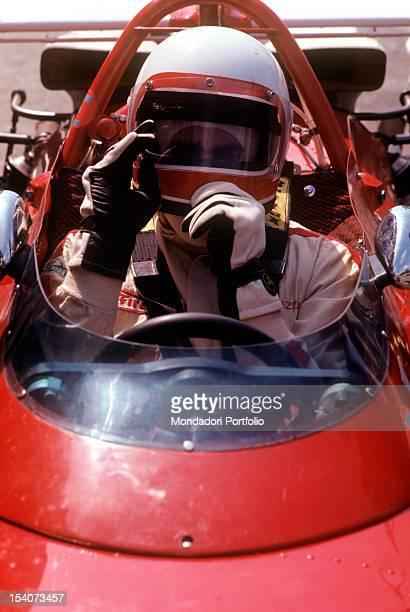 The Swiss racing car driver Clay Regazzoni fixing his helmet sitting on board a Ferrari 312 B Monza August 1970