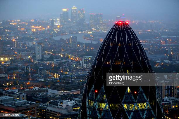 The Swiss Re Insurance building also known as 'the Gherkin' foreground and the towers of the Canary Wharf business district are seen against the city...