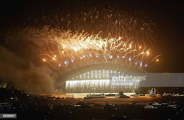 The Sydney harbour bridge is lit up by fireworks during New Years Eve Celebrations in Sydney Harbour December 31, 2003 in Sydney, Australia. A crowd...