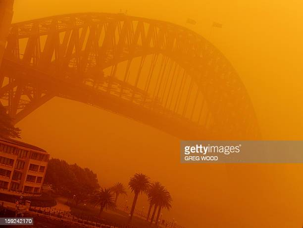 The Sydney Harbour Bridge is shrouded in an eerie blanket of dust on September 23 2009 Sydney's cars and buildings turned orange as strong winds blew...