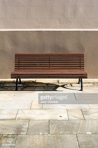 A park bench in a sandstone courtyard is a place to rest in the sun.