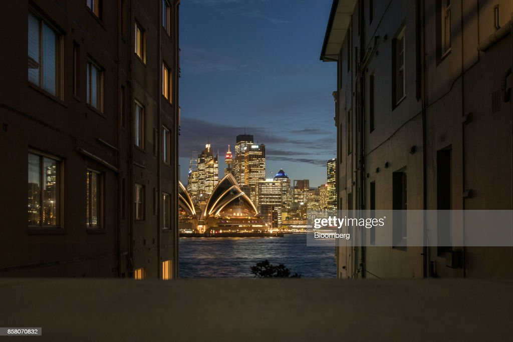 The Sydney Opera House, center left, and buildings in the financial district are seen between residential blocks as they stand illuminated at dusk in Sydney, Australia, on Friday, Sept. 29, 2017. A bungled transition from coal to clean energy has left resource-rich Australia with an unwanted crown: the highest power prices in the world. Photographer: Cole Bennetts/Bloomberg via Getty Images