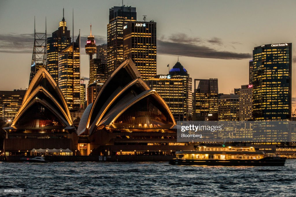 The Sydney Opera House, foreground, and buildings in the financial district stand illuminated at dusk in Sydney, Australia, on Friday, Sept. 29, 2017. A bungled transition from coal to clean energy has left resource-rich Australia with an unwanted crown: the highest power prices in the world. Photographer: Cole Bennetts/Bloomberg via Getty Images