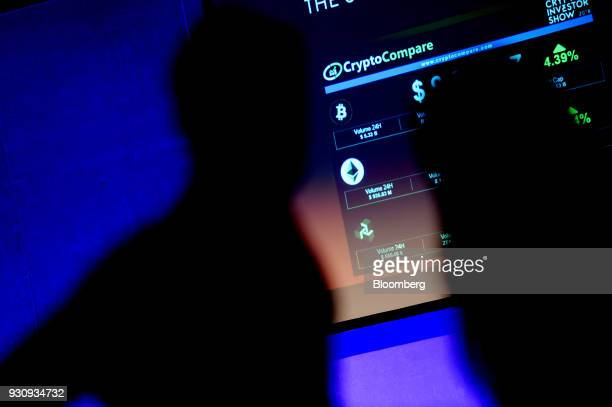 The symbols of Bitcoin and Ethereum cryptocurrencies sit displayed on a screen during the Crypto Investor Show in London UK on Saturday March 10 2018...