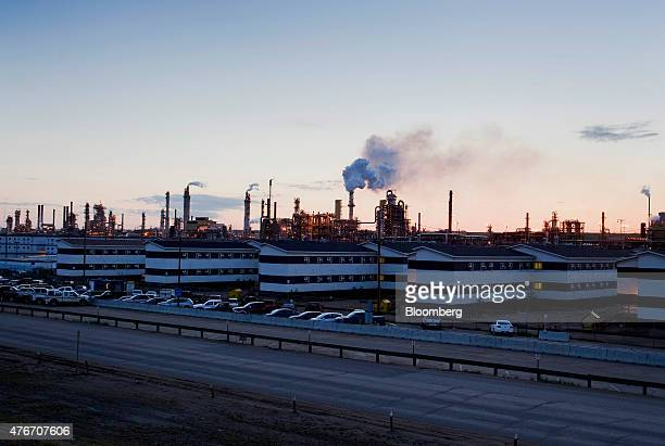 The Syncrude Canada Ltd upgrader plant stands past housing at the company's mine in the Athabasca Oil Sands near Fort McMurray Alberta Canada on...