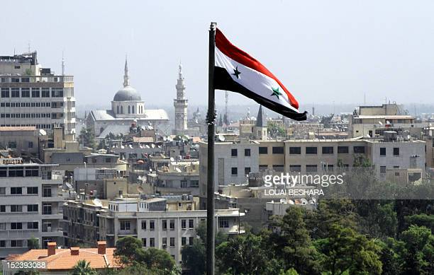 The Syrian flag flutters above Damascus on September 20 2012 Rebel fighters shot down a helicopter in a battleground town near Damascus today a...