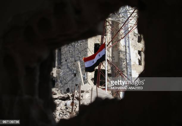 The Syrian national flag rises in the midst of damaged buildings in Daraa-al-Balad, an opposition-held part of the southern city of Daraa, on July...