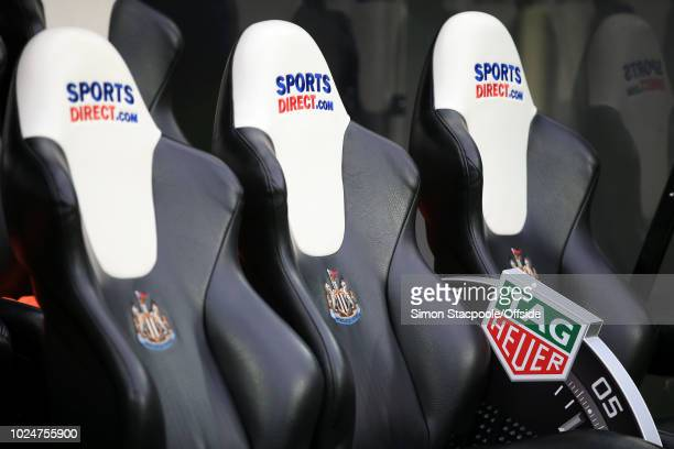 The Tag Heuer logo on the fourth official's sponsored time indicator board seen alongside the Sports Direct logos on the dugouts seats during the...