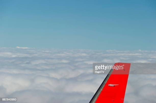 The Tail Fin of an Airplane flying over clouds at high altitude.