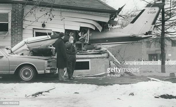 The tail of a twinengined Cessna plane sticks out of the wrecked Oshawa house of Earl Moore and his wife Verna while Police Constable Dave Fitzgerald...