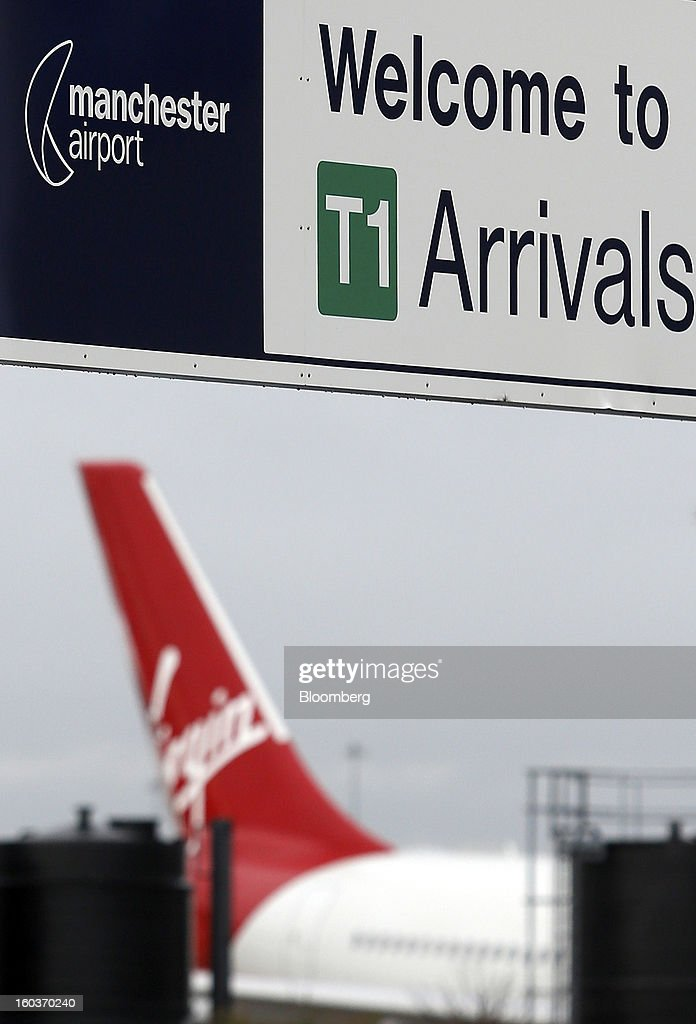 The tailfin of a Virgin Atlantic aircraft is visible beyond a sign welcoming travelers to Manchester airport in Manchester, U.K., on Tuesday, Jan. 29, 2013. Manchester Airports Group, owner of Britain's busiest airport outside London, is buying Stansted from Heathrow Airport Ltd., which is ceding 100 percent of Stansted to comply with regulatory requirements. Photographer: Paul Thomas/Bloomberg via Getty Images