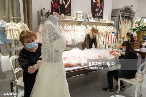 The tailoring staff of designer Mariella Gennarino wear masks and protective gloves while they work on a formal dress in the atelier in Catania...