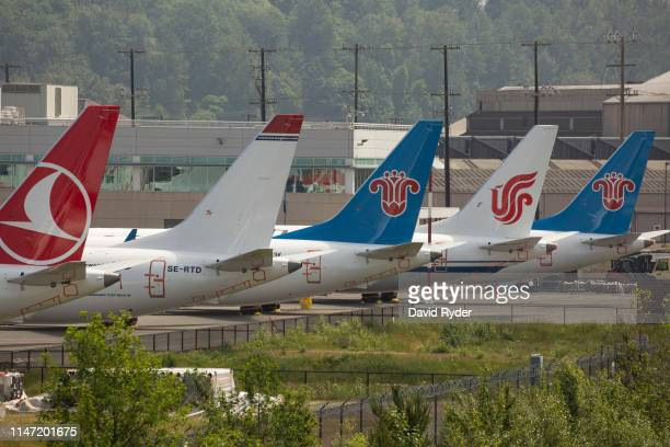 The tails of Boeing 737 MAX airplanes are seen as they sit parked at a Boeing facility adjacent to King County International Airport known as Boeing...