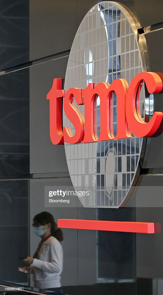 The Taiwan Semiconductor Manufacturing Co. (TSMC) logo is displayed as an employee is reflected entering the company's headquarters in Hsinchu, Taiwan, on Wednesday, Jan. 16, 2013. Taiwan Semiconductor Manufacturing Co., the world's largest supplier of made-to-order chips, is scheduled to announce company results tomorrow. Photographer: Maurice Tsai/Bloomberg via Getty Images