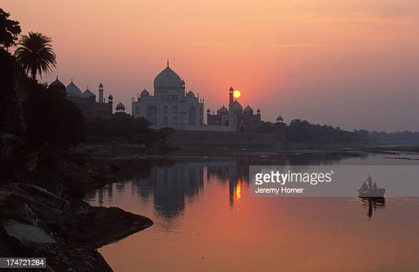 The Taj Mahal stands majestic over the Yamuna River in the evening twilight
