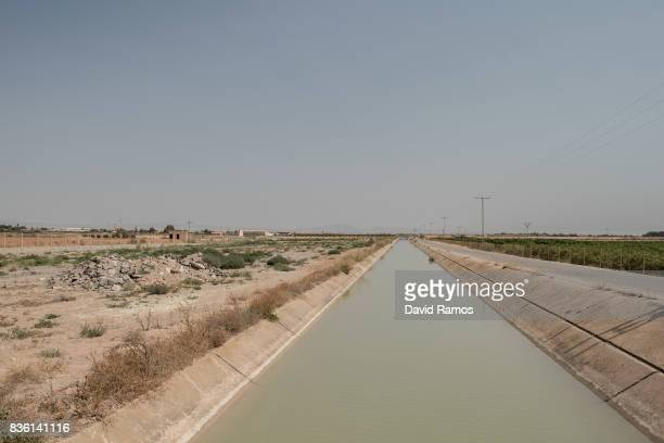 The TajoSegura interbasin water transfer canal is seen crossing the fields of the agricultural region of El Campo de Cartagena on July 28 2017 in Los...