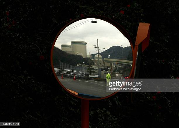 The Takahama Nuclear Power Station is seen in a roadside mirror which runs by Kansai Electric Power Co on March 9 2012 in Takahama Japan Only two of...