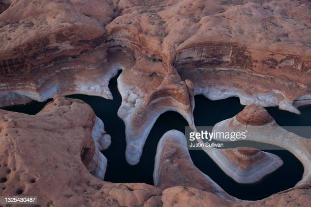 """The tall bleached """"bathtub ring"""" is visible on the rocky banks of Lake Powell at Reflection Canyon on June 24, 2021 in Lake Powell, Utah. As severe..."""