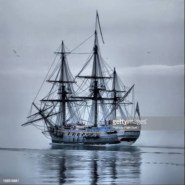 The tall ship Götheborg sailing in Valderøy fjord on a calm and foggy day, almost lost in the mist. The ship is a Swedish three-master