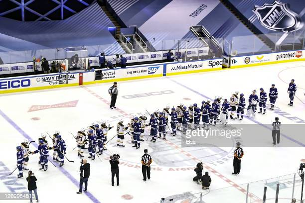 The Tampa Bay Lightning shake hands with the Boston Bruins after the Lightning's 32 victory during the second overtime period in Game Five of the...