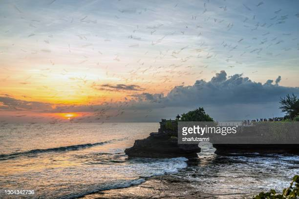 the tanah lot temple is on offshore rock which has been shaped continuously over the years by the ocean tide. - shaifulzamri stock pictures, royalty-free photos & images