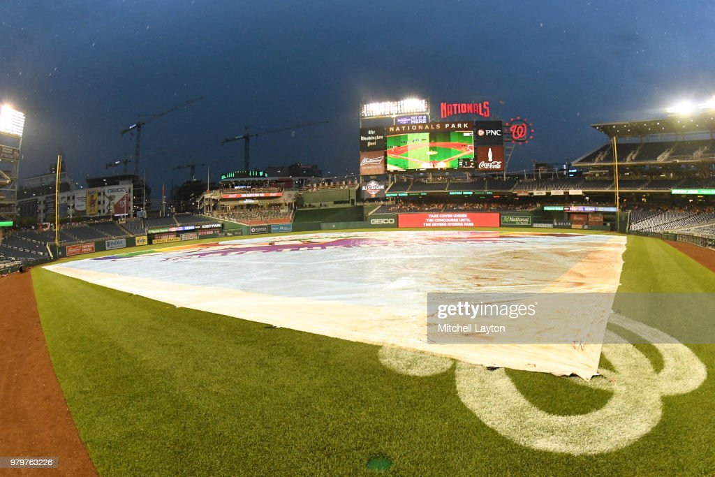 The tarp covers the field as the game into a rain daly after the fourth inning during a baseball game between the Washington Nationals and the Baltimore Orioles at Nationals Park on June 20, 2018 in Washington, DC.