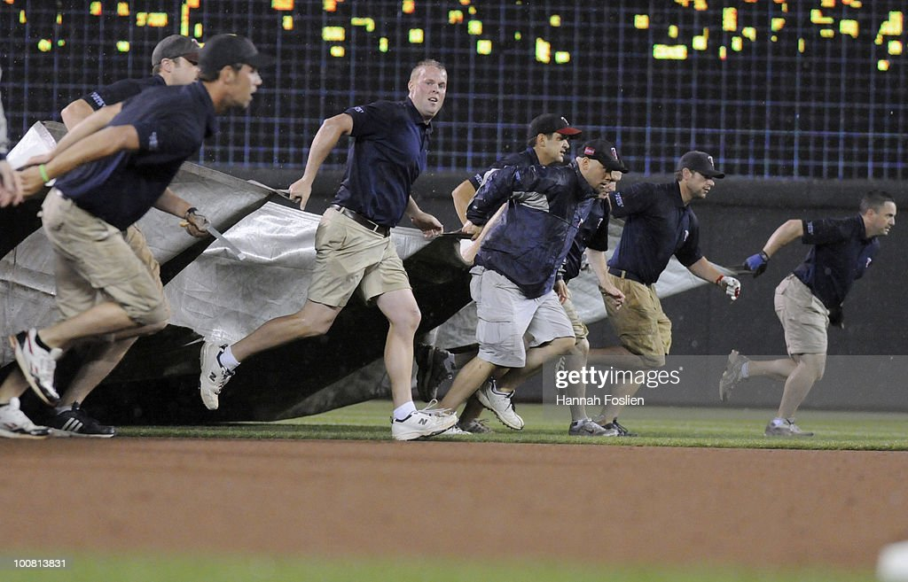 The tarp crew for the Minnesota Twins pulls the tarp for the first rain delay following the fifth inning against the New York Yankees during their game on May 25, 2010 at Target Field in Minneapolis, Minnesota.
