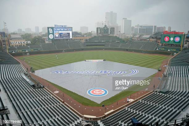 The tarp sits on the field before the game between the Chicago Cubs and the St Louis Cardinals as rain moves through the area at Wrigley Field on...