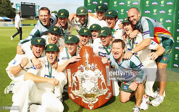 The Tasmania Tigers team celebrate with the Shield Shield after winning on day five of the Sheffield Shield final match between the Tasmanian Tigers...