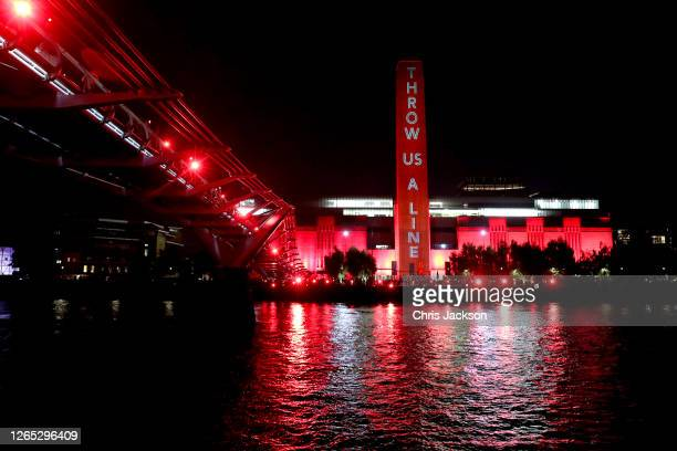The Tate Modern is lit up in red as supporters also shine red lights from the Millennium Bridge as part of the #WeMakeEvents' 'Throw Us a Line...