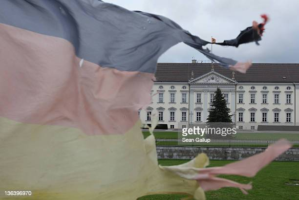 The tattered German flag of a single protester waves in the wind in front of Schloss Bellevue presidential palace on January 4 2012 in Berlin Germany...