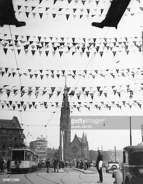 The Tauenzienstrasse decorated with flags for the Olympic Games in the middle the Kaiser Wilhelm Memorial Church ca 1936 Photographer Eric Borchert...