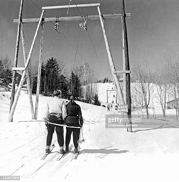 The TBar ski lift at the Laurentian Mountains ski resort pulls skiers slowly up the mountain Montreal Quebec Canada early 1950s