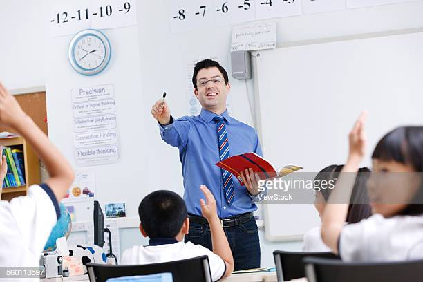 The teacher is talking with primary school students in the class