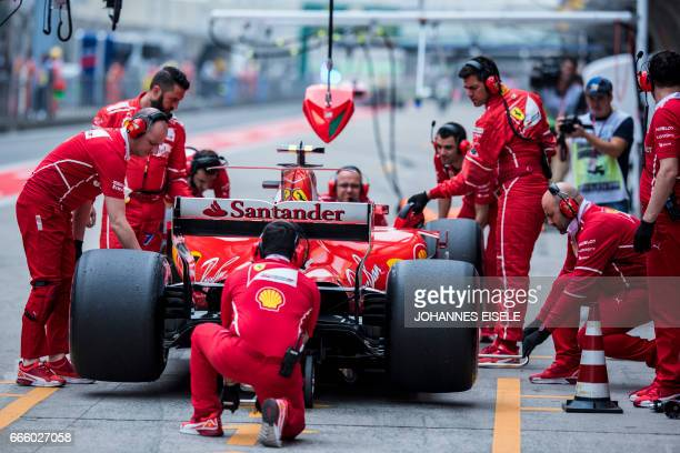 The team for Ferrari's Finnish driver Kimi Raikkonen work on his car during the third practice session for the Formula One Chinese Grand Prix in...