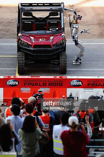 The Team Kaist HUBO robot from South Korea climbs out of a Polairs vehicle during the first day of the Defense Advanced Research Projects Agency...