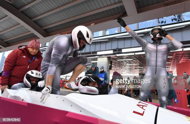 The team led by Latvia's Oskars Melbardis celebrates after the 4man bobsleigh heat 4 final run during the Pyeongchang 2018 Winter Olympic Games at...