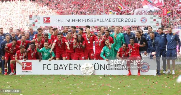 The team of Bayern Munich pose with the trophy following the Bundesliga match between FC Bayern Muenchen and Eintracht Frankfurt at Allianz Arena on...